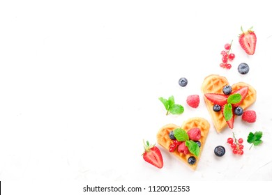 Heart shape belgium waffles with assorted berries mix, strawberry, blueberry, raspberry and red currant decorated with mint leaf on white ceramic plate. Close up, copy space, background, top view.