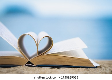 The heart shape from the book against the blurred sea background Love concept
