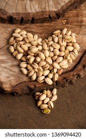 Heart shape broken made out of roasted pistachios spread on wooden planks and wood background