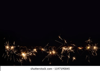 A lot of heart shape burning sparklers, isolated on black background. Birthday party background. Bottom border a lot of copy space, room for text.