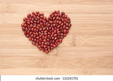 Heart shape by red beans. Common ingredient in Asian cuisine, red beans on wooden background.