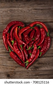 Heart shape by red pepper on wooden background