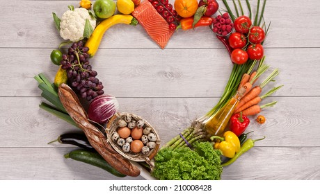 Heart shape by various vegetables and fruits / food photography of heart made from different fruits and vegetables on wooden table