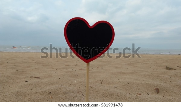 heart shape chalkboard on sandy beach. Composition of Nature. low light