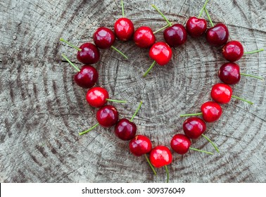 Heart shape cherries on the wooden background