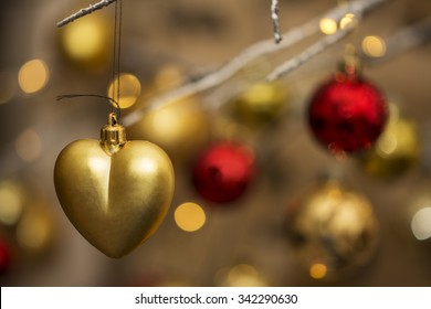 Heart shape christmas bauble hanging from contemporary christmas tree