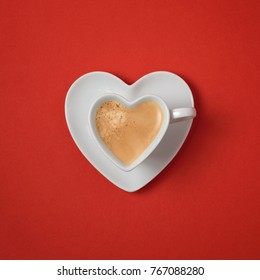 Heart shape coffee cup over red background. View from above