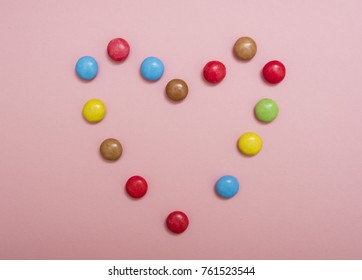 Heart shape from Colorful smarties on pink background