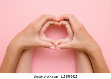 Heart shape created from little girl's hands and her mother's hands on the pink background. Lovely emotional, sentimental moment. Love, happiness and safety concept.