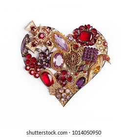 Heart shape cutout with red and golden color jewellery on white background. Valentine`s Day, Woman`s Day concept.