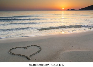 Heart shape drawn on a  sandy beach at sunrise on the beautiful island of Thassos, Greece.