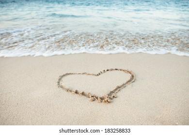 Heart shape drawn in sand on beach