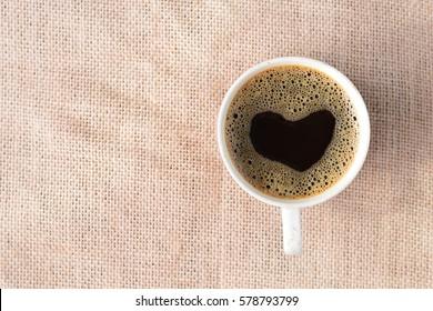 heart shape foam bubble in coffee cup on sack background