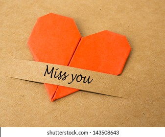 """The heart shape of folded paper on brown screen with """"miss you"""" on tab"""