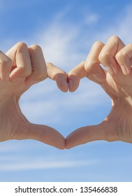 Heart shape formed by hands on blue sky background