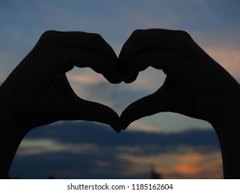 Heart shape of hands against beautiful sky on evening night