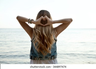 Heart shape hands, blonde hair with low sephia effect. Symbol of