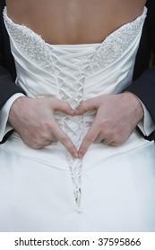 Heart shape hands of groom around bride at wedding
