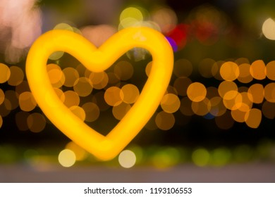 Heart shape, LED light design style for love symbol, yellow and orange icon with bokeh bacdrop, copy space, de focus