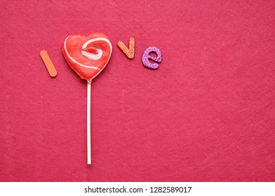 A heart shape lollipop forming a part of the word love