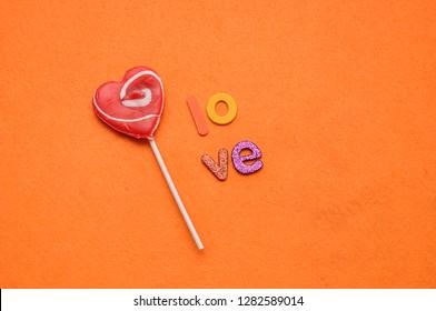A heart shape lollipop with the word love