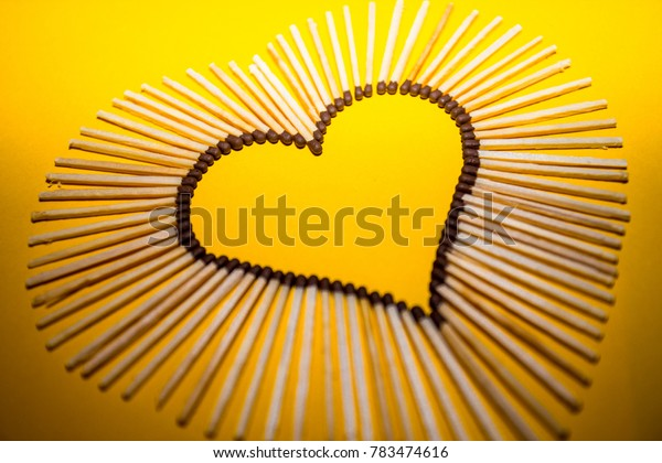 Heart shape of love from matches on a yellow background. Romantic symbol. Love concept