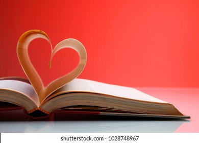 Heart shape made from book with red background
