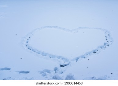 heart shape made by foot in the snow on a frozen lake