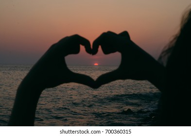 Heart shape made by woman hands at sunset on the sea.