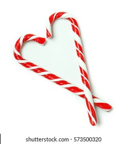 Heart shape made of candy canes on white background