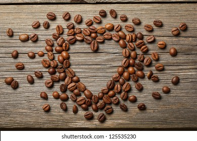 Heart shape made from coffee beans on wooden surface.