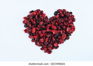 Heart shape made of dried cranberry on a white background.