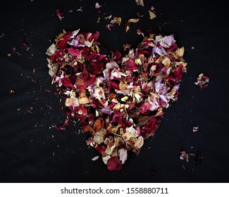 A heart shape made from dried rose petals and orchids with pieces scattered about
