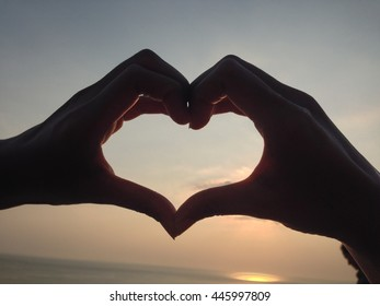 Heart shape made with hands at sunset