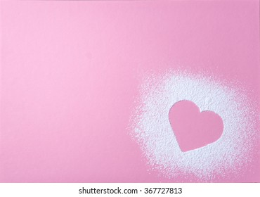 Heart shape made of icing sugar on pink natural paper background