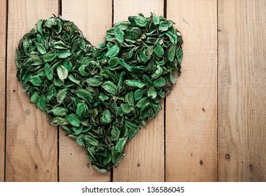 heart shape made of leaves on wooden background with copyspace