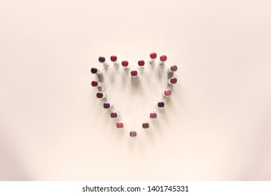 Heart shape made of lipstick collection positioned on peach background. Flat lay concept. Lot of space for copy.