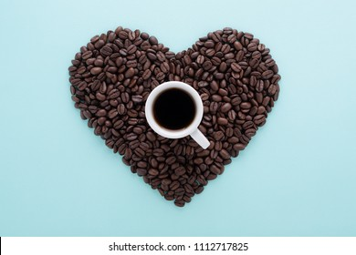 Heart shape made of perfect coffee beans & a cup of black coffee on blue background. Flat lay, minimal. Love coffee espresso concept.