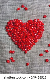 heart shape made of pomegranate seeds on a cloth background