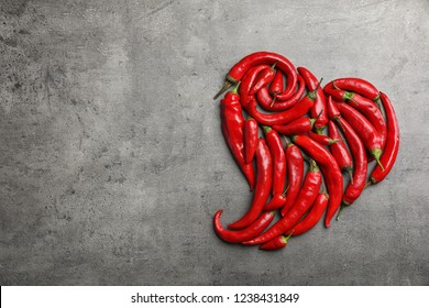 Heart shape made of red chili peppers on gray background, top view with space for text