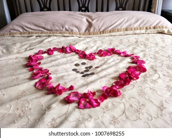 Heart shape made from rose petals with coins on the bed for wedding ceremony in Thailand