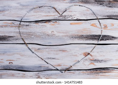 Heart shape made from screws on wooden background. Different screws forming heart shape on wooden boards. Space for text.