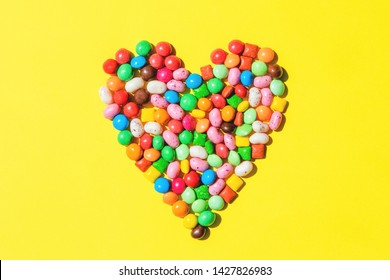 Heart shape made of small colorfull candies on bright yellow background. Sweets for birthday, sweetest day concept. Valentine's day design. Top view, flat lay.
