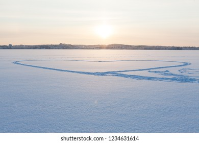 Heart shape made in snow by walking at frozen lake