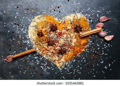 Heart shape made from spices with cinnamon and garlic arrow on slate background
