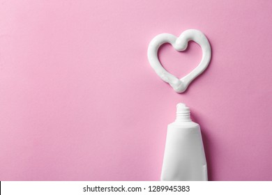 Heart shape made of toothpaste near tube and space for text on color background, top view