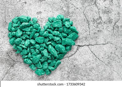 heart shape made of turquoise decorative stones on a gray surface with cracks. Love, passion, feelings concept. minimalism. top view. horizontal image