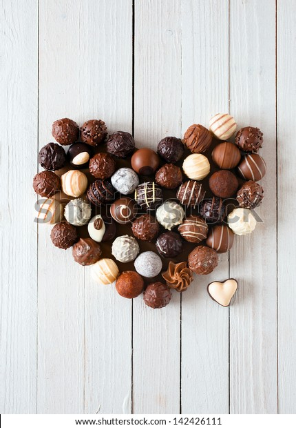 Heart shape made with various types of chocolate truffles over a white wooden table
