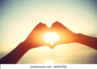 Heart shape making of hands against bright sea sunrise and sunny golden way at water
