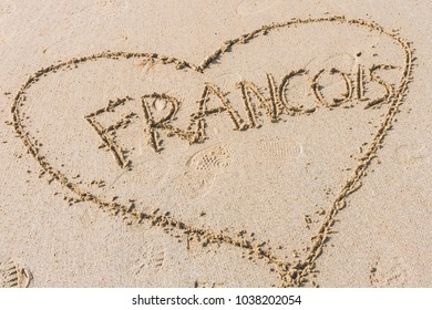 Heart shape with male name inside hand written on wet sand on sunny day. Concept of love and romance
